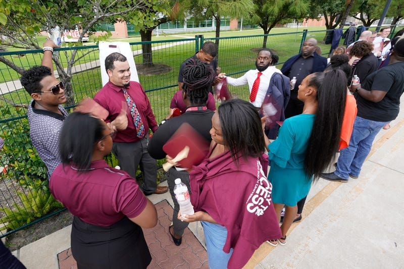 Texas Southern University students wait in the heat to enter a Democratic presidential primary debate hosted by ABC Thursday, Sept. 12, 2019, at Texas Southern University in Houston.