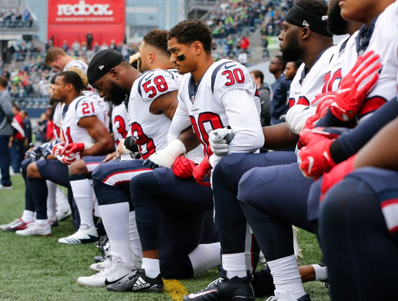 Members of the Houston Texans, including Kevin Johnson, No. 30, and Lamarr Houston, No. 58, kneel during the national anthem before the game at CenturyLink Field on Oct. 29, 2017, in Seattle.