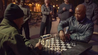 "Chess grandmaster Maurice Ashley (right) plays chess with a man named ""Wilson"" in New York City's Washington Square Park. YouTube screenshot"