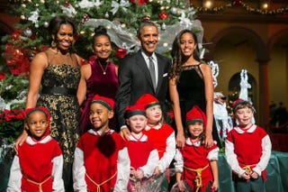 "President Barack Obama, first lady Michelle Obama, and their daughters Sasha and Malia pose with ""elves"" prior to the taping of TNT's Christmas in Washington program on Dec. 14, 2014, in Washington, D.C.Kristoffer Tripplaar-Pool/Getty Images"