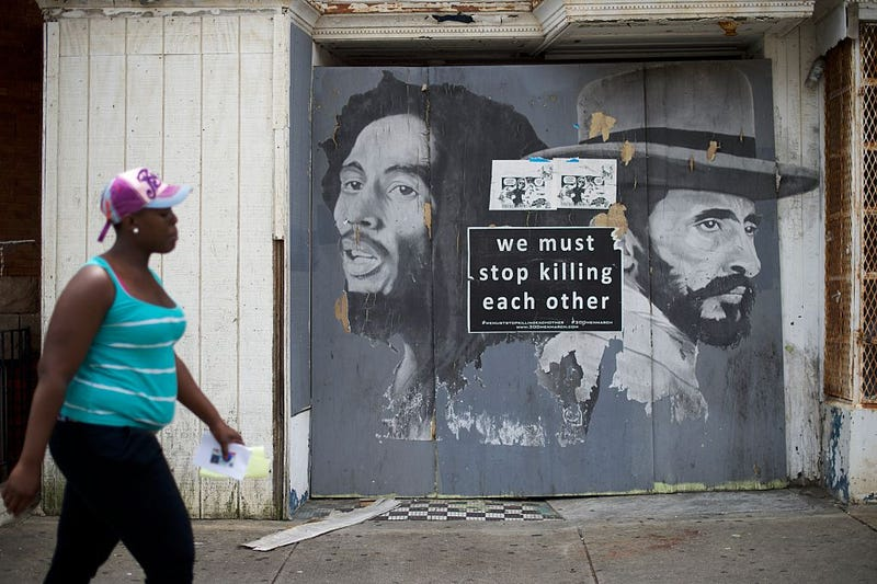 A woman walks past a 'We Must Stop Killing Each Other' sign  on June 23, 2016, in Baltimore.  (Mark Makela/Getty Images)