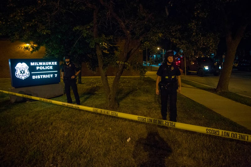Police officers stand guard at Milwaukee's District 7 police station as angry crowds take to the streets for a second night Aug. 14, 2016, to protest an officer-involved killing.Darren Hauck/Getty Images