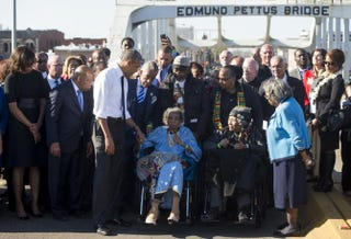 President Barack Obama speaks to Amelia Boynton Robinson (center), one of the original marchers, alongside first lady Michelle Obama (left) and U.S. Rep. John Lewis (D-Ga.), one of the original marchers, after leading a walk across the Edmund Pettus Bridge to mark the 50th anniversary of the Selma-to-Montgomery civil rights marches in Selma, Ala., March 7, 2015.SAUL LOEB/AFP/Getty Images
