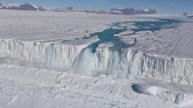 An enormous waterfall at the Nansen Ice Shelf channels summertime meltwater into the ocean, a process that seemingly protects the shelf from collapse. Image courtesy of Jonathan Kingslake
