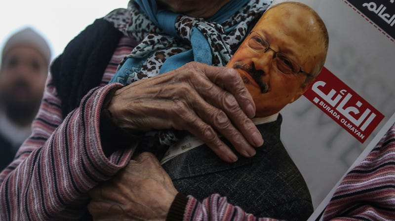 A woman holds a poster during the funeral for dissident Saudi writer Jamal Khashoggi.