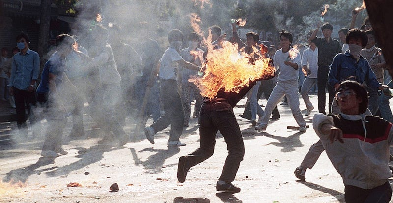 A South Korean student engulfed in flames runs for safety as his compatriots launch home-made firebombs toward riot police during anti-government, anti-Olympic demonstrations at Korea University in Seoul, South Korea on Sept. 29, 1988. (Photo credit: AP)
