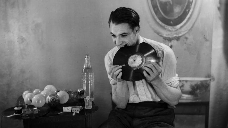 1938: A man chews up a gramophone record. Beside him is a table on which are light bulbs waiting to be eaten.