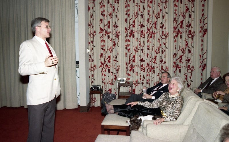 Tom Clancy speaking in the White House screening room while First Lady Barbara Bush laughs and President Bush looks on (February 19, 1990, George Bush Presidential Library and Museum)