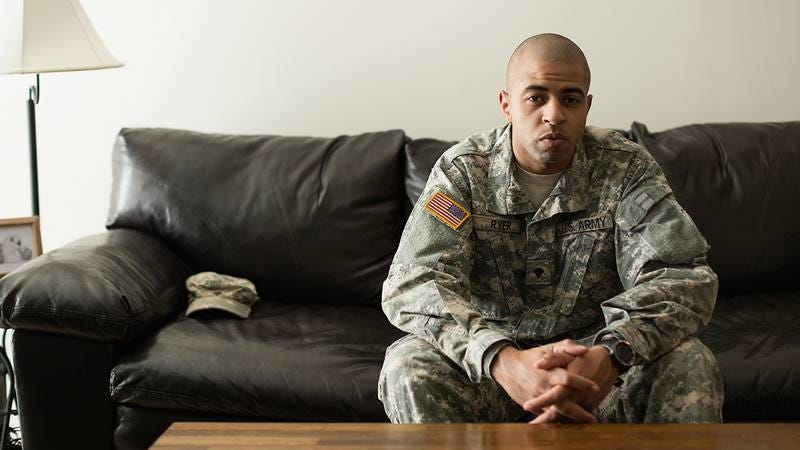A U.S. soldier sitting on a couch in uniform.