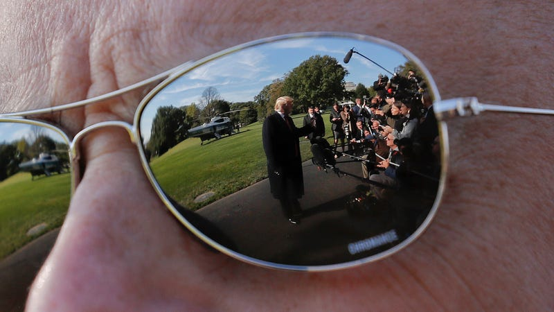 President Donald Trump on the South Lawn of the White House in October 2018, as seen reflected in the sunglasses of a Secret Service agent.