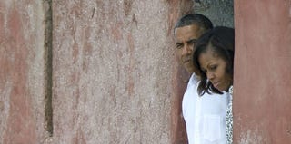The president and the first lady peer out of the Door of No Return while touring Africa. (Jim Watson/AFP/Getty Images)