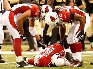 Kurt Warner lies injured during a 2010 game against theNew Orleans Saints. (Ronald Martinez/Getty Images)