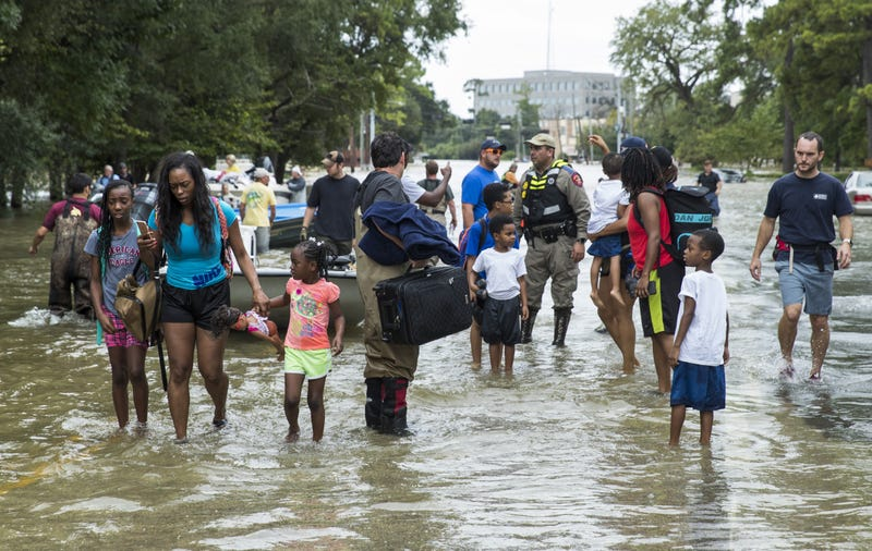 Families walk out of the water in west Houston on Aug. 30, 2017, after being rescued from their flooded homes and apartments because of Hurricane Harvey. (Erich Schlegel/Getty Images)