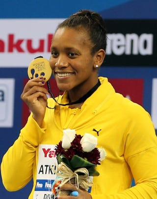 Alia Atkinson of Jamaica poses with her gold medal after winning the women's 100 breaststroke during the 12th FINA World Swimming Championships in Doha, Qatar, on Dec. 6, 2014.KARIM JAAFAR/AFP/Getty Images