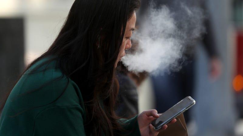 A pedestrian smokes an e-cigarette on November 08, 2019 in San Francisco, California.