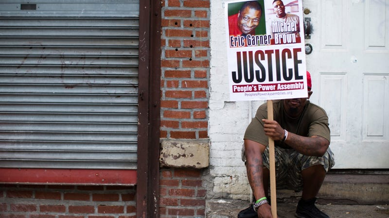 A protester holds up a sign with images of both Eric Garner and Michael Brown, both killed at the hands of police officers, during an August 2014 action on Staten Island in New York City.