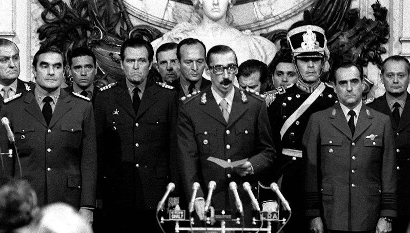 """Gen. Jorge Rafael Videla, who would go on to disappear thousands of citizens in Argentina's """"Dirty War,"""" is sworn-in as president in 1976 next to members of the junta that overthrew Argentinian president Isabel Peron. Image via AP Photo."""