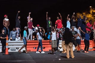Protesters react to a police helicopter during protests in the early hours of Sept. 21, 2016, in Charlotte, N.C., in response to the fatal police shooting of Keith Lamont Scott. Sean Rayford/Getty Images