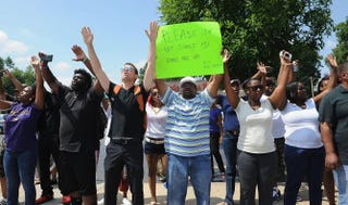 """Protesters stand with their arms in the air during a protest of the shooting death of 18-year-old Michael Brown by a Ferguson, Mo., police officer, outside Ferguson Police Department headquarters Aug. 11, 2014. One protester holds a sign that reads, """"Please do not shoot. My hands are up.""""Michael B. Thomas/Getty Images"""