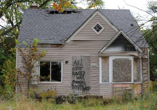 """An abandoned home seen Sept. 30, 2013, in Detroit, is decorated with a piece of fencing and graffiti that declares, """"All I ever wanted was a white picket fence.""""MIRA OBERMAN/AFP/Getty Images"""