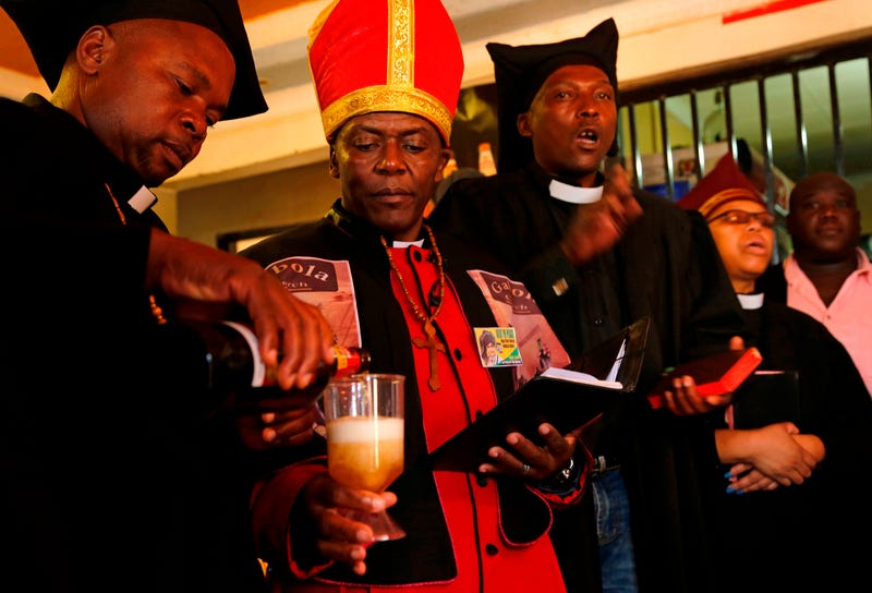 Leader of the Gabola Church Tsietsi Makiti (second from left) prepares to baptize newcomers to the church during a service in a bar in Orange Farm, south of Johannesburg, April 15, 2018.