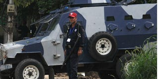 A Pakastani security stands next to an armored vehicle outside a U.S. consulate. (Arif Ali/AFP/Getty Images)