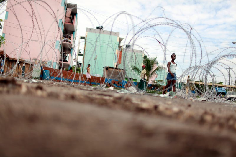 In this May 30, 2010, file photo, a girl walks behind a concertina wire at a military checkpoint in the Tivoli Gardens neighborhood of Kingston, Jamaica, during a state of emergency on the Caribbean island. (Rodrigo Abd, file/AP Images)