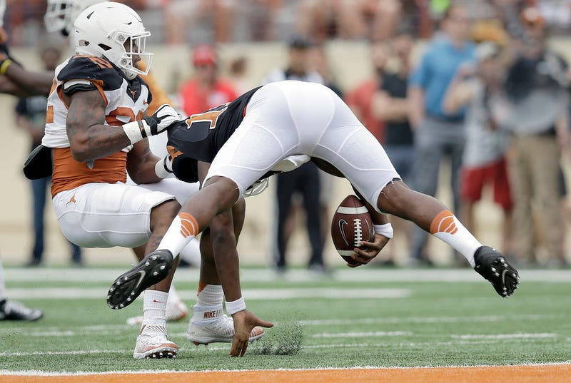 Texas quarterback Tyrone Swoopes gets sacked by Texas defensive end Quincy Vasser in the spring game. Via AP.