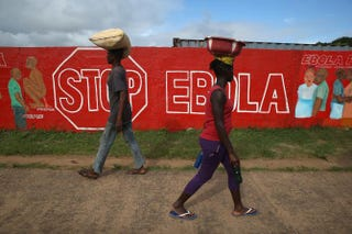 People pass an Ebola-awareness mural on Oct. 2, 2014, in Monrovia, Liberia.John Moore/Getty Images