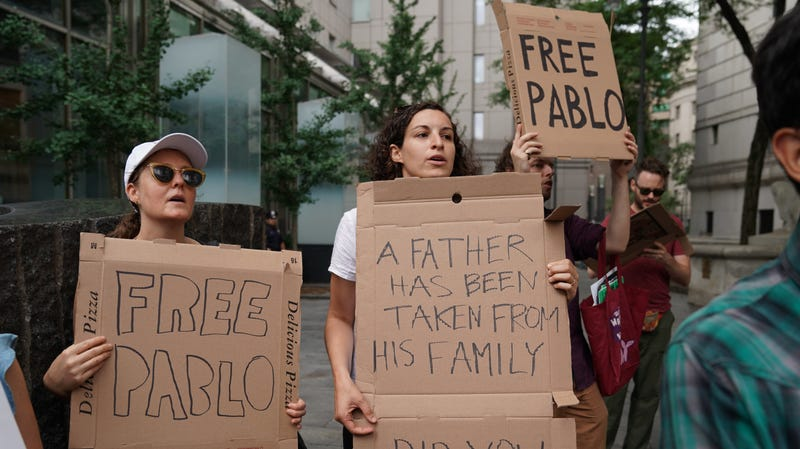 Protesters, with slogans written on pizza delivery boxes, demonstrate outside Federal Court on July 24 in New York