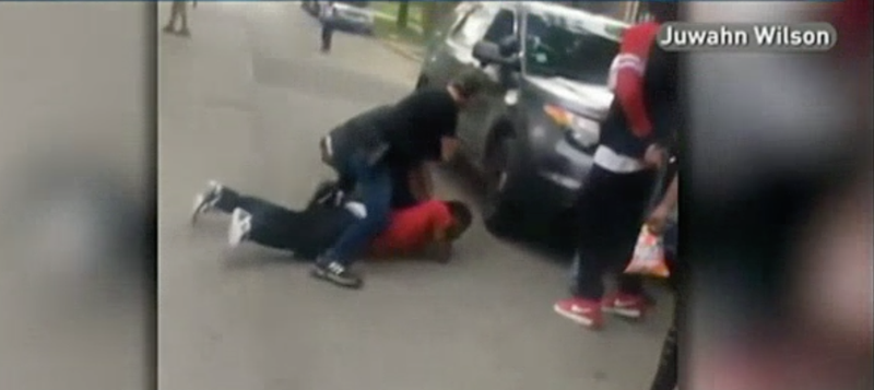 A plainclothes police officer is seen straddling Jermaine Milan in Chicago. (NBC Chicago)