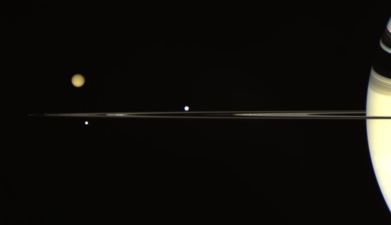 Tethys (right), Titan and Enceladus (top and bottom left) shown above and below the plane of Saturn's rings. Image: NASA/JPL/Space Science Institute, Processed by Kevin M. Gill