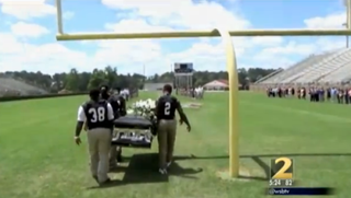 Coffee County High School football players carry their teammate across the field.WBS-TV