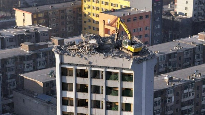 Illustration for article titled Why Is This Excavator Excavating A 12-Story Building From The Top Down?