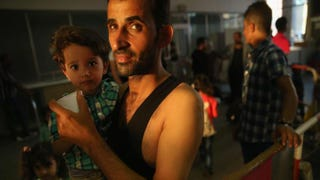 A migrant from Syria holds one of his children in a holding area after arriving at a rail station in Munich, Germany, and being detained by police Aug. 29, 2015. Several governors in the U.S. have come out against allowing refugees fleeing the war in Syria to come to America.Sean Gallup/Getty Images