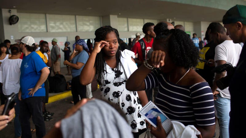 Two women cry after arriving at the Port of Palm Beach on the cruise ship Grand Celebration Sept. 7, 2019, in West Palm Beach, Fla. The ship arrived with hundreds of evacuees impacted by Hurricane Dorian in the Bahamas.