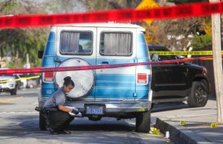 A police officer investigates the scene near Pearson Park in Anaheim, Calif., on Feb. 27, 2016, after three counterprotesters were stabbed while clashing with Ku Klux Klan members staging a rally. Thirteen people were arrested.RINGO CHIU/AFP/Getty Images