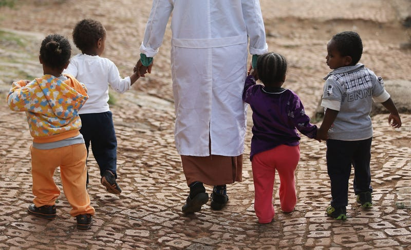 A woman walks with orphans at the Agoheld orphanage, hospital, training center and school on March 19, 2013, in Addis Ababa, Ethiopia. (Sean Gallup/Getty Images)