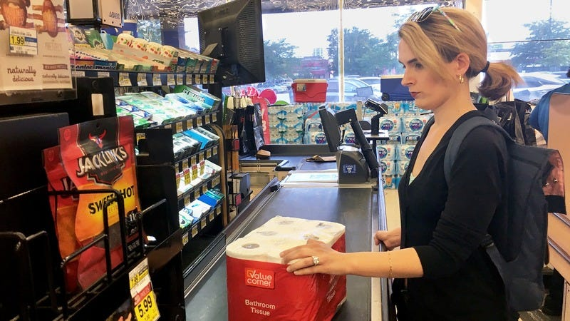 A woman with a huge engagement ring in the check out aisle to buy single-ply toilet paper.