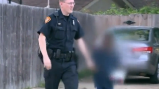Police in Memphis, Tenn., shown escorting the reported 8-year-old boy away from a home after they say he was found locked to a shed.    WREG News Screenshot