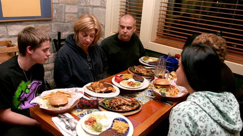 Family members try in vain to avert their eyes from the crackling plate of chicken and vegetables.