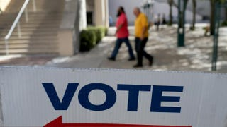 A sign points to the early-voting station set up at a Miami government building Oct. 28, 2014.Joe Raedle/Getty Images