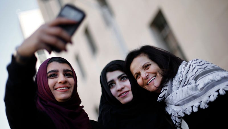 Manar Daghash, from left, and Sundous Daghash pose for a selfie with Rasmea Odeh after leaving federal court in Detroit Thursday, March 12, 2015. Image via AP.