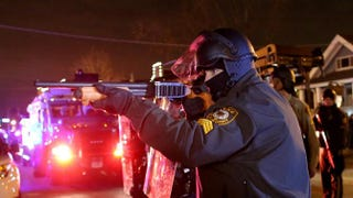 A police officer points a shotgun at protesters during a demonstration in Ferguson, Mo., Nov. 24, 2014. Justin Sullivan/Getty Images