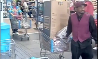 Tarus Scott (in the red) leaves Wal-Mart with the cart full of toysYouTube