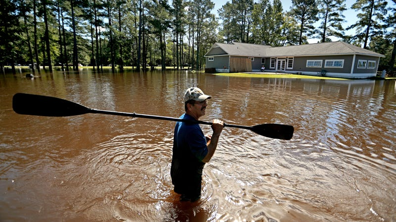 A man stands in front of his North Carolina home as floodwaters rise after Hurricane Florence