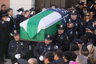 Pallbearers carry the casket of Officer Rafael Ramos of the New York City Police Department out of Christ Tabernacle Church on Dec. 27, 2014, in Queens, N.Y. Ramos and Officer Wenjian Liu were attacked without warning and fatally shot as they sat in a marked police car in Brooklyn on Dec. 20.Kevin Hagen/Getty Images