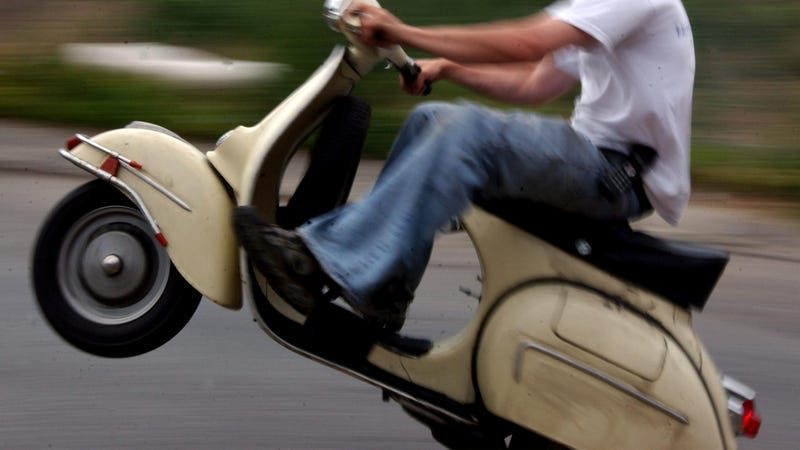 A man pops a wheelie on a scooter, a type of motorcycle that is similar to but distinct from a moped.