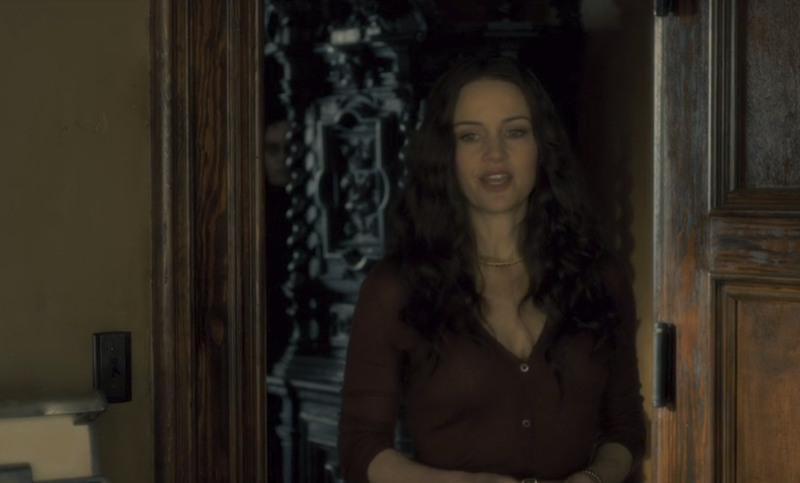 Some dead guy (background) and Carla Gugino (foreground) in The Haunting Of Hill House