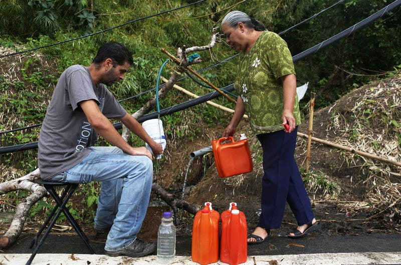 Migdalia Aceuedo and her son Mathews Rosado Aceuedo collect spring water for their house in Utuado, Puerto Rico, on Oct. 10, 2017, by a downed power line nearly three weeks after Hurricane Maria hit the island. (Mario Tama/Getty Images)